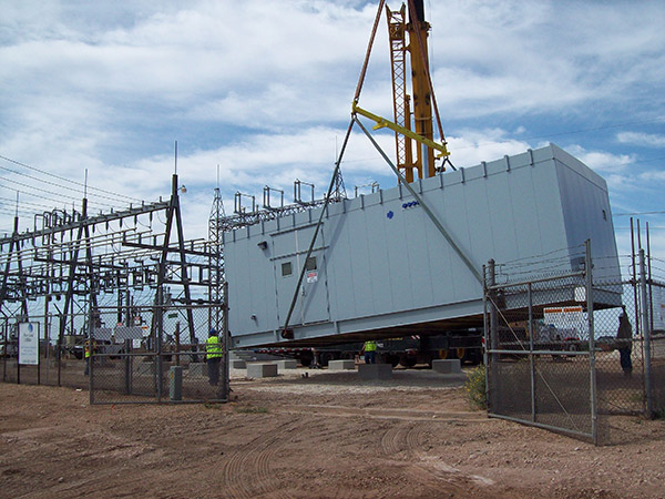 A control house is being lowered onto its foundation at a substation construction site.