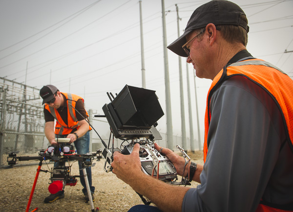 Unmanned aerial vehicle operator reviews device settings. Another pilot adjusts the drone on the ground.